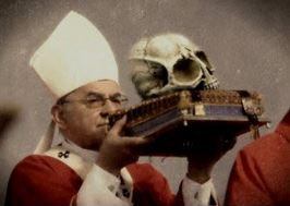 Catholic Bishop Holding Fallen Angel Skull On Bible In Service